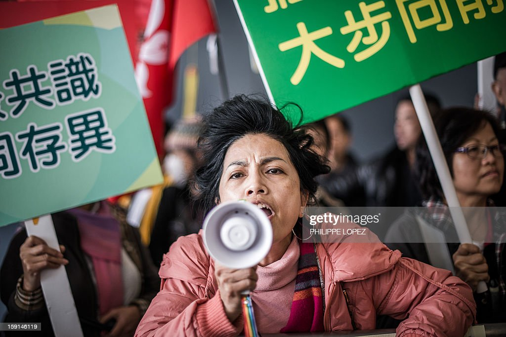 A supporter of of Hong Kong Chief Executive Leung Chun-ying uses a bullhorn to shout slogans against pro-democracy lawmakers and their supporters during a protest in Hong Kong on January 9, 2013. Pro-democracy lawmakers were expected to table an impeachment motion on January 9 against chief executive Leung Chun-ying, demanding him to quit over a housing scandal. AFP PHOTO / Philippe Lopez