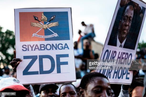 Supporter of of Zimbabwe's incoming president Emmerson Mnangagwa hold his portrait and a placard hailing the ZDF at Zimbabwe's ruling ZanuPF party...