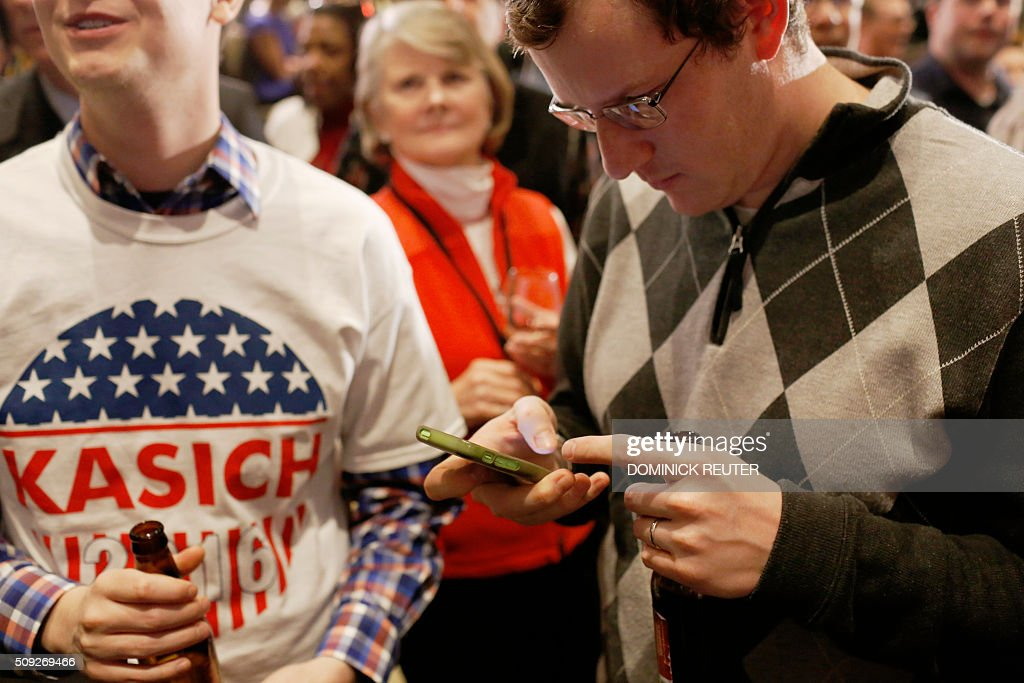 A supporter of Ohio Governor and Republican presidential candidate John Kasich checks his phone as he awaits voting results during a primary election watch party, February 9, 2016, in Concord, New Hampshire. Political novice Donald Trump won New Hampshire's presidential primaries, US media projected, with a fierce battle for second place among Ohio Governor John Kasich, former Florida governor Jeb Bush, Senators Ted Cruz and Marco Rubio. / AFP / DOMINICK REUTER
