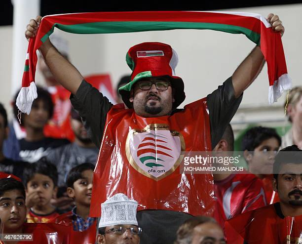 A supporter of Oman's national team waves the national flag during the friendly football match between Oman and Malaysia at the AlSeeb Stadium in...