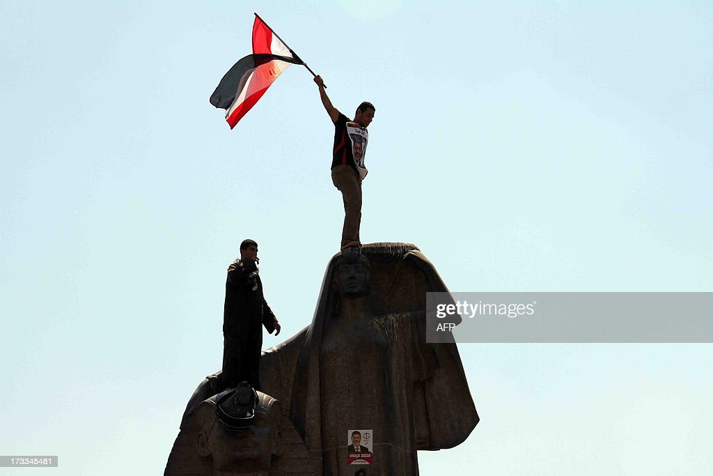 A supporter of ousted Egyptian president Mohamed Morsi waves his national flag after climbing with a fellow demonstrator on a statue as thousands of demonstrators march towards Cairo University to show their support on July 12, 2013. Tens of thousands of Morsi' supporters gathered vowing to keep fighting for his reinstatement, as rival rallies defending his overthrow underlined Egypt's bitter divisions. AFP PHOTO/KHALED KAMEL