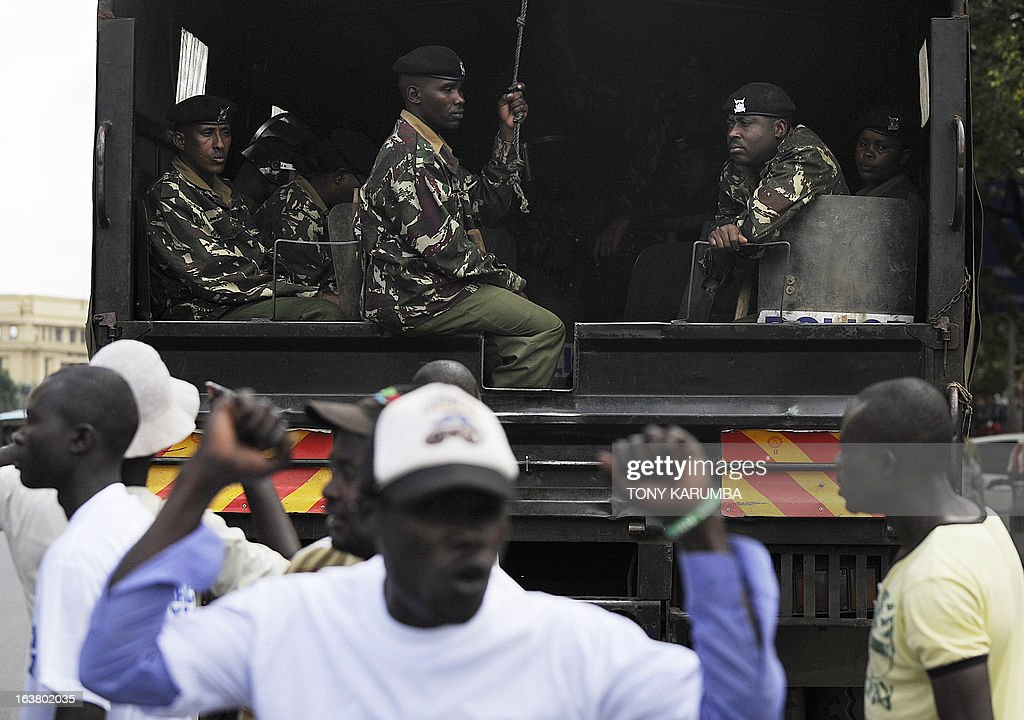A supporter of outgoing Kenyan Prime minister Raila Odinga raises his hands as he shouts in front of the police on March 16, 2013 outside Kenya's Supreme Court building in Nairobi, where police used tear gas to disperse around 100 people demonstrating in favour of Odinga. Odinga, who was narrowly defeated in presidential polls by Uhuru Kenyatta, filed a formal challenge Saturday against the result. Officials from Odinga's Coalition for Reform and Democracy (CORD) filed the suit at the Supreme Court after Odinga spoke to supporters and journalists in front of his offices. AFP PHOTO/Tony KARUMBA