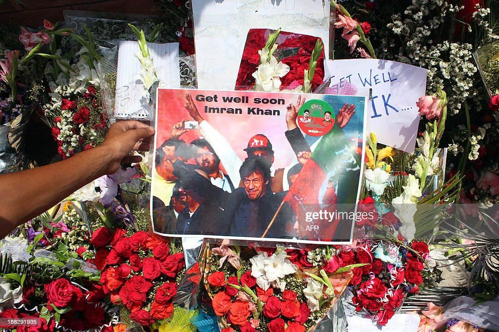 A supporter of Pakistani politician and former cricketer Imran Khan, places a picture outside a hospital where Khan is admitted in Lahore on May 8, 2013. Khan has been advised to rest for a week after sustaining skull and back injuries in a fall at an election campaign rally, a hospital official said. The former cricket star was admitted to the private Shaukat Khanum hospital that he founded in Lahore on May 7 after falling off a lift taking him to the stage at a rally ahead of Pakistan's general election on Saturday. AFP PHOTO / TALHA ALI