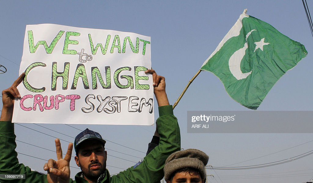 A supporter of Pakistani religious leader Tahir-ul Qadri holds a sign during a protest march in Lahore on January 13, 2013. An influential Pakistani preacher on Sunday led thousands of supporters at the start of a protest march on the capital Islamabad to demand key reforms before looming elections. AFP PHOTO/Arif ALI