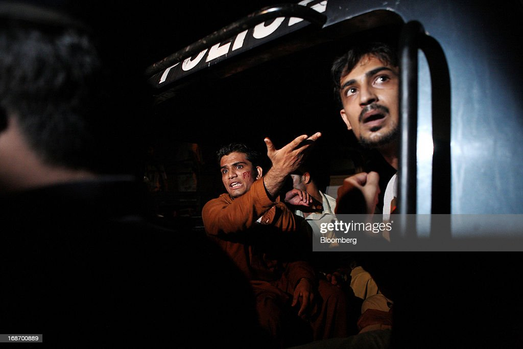 A supporter of Pakistan's Tehreek-e-Insaf (PTI) chairman Imran Khan gestures from the back of a police vehicle after being detained during a demonstration in Karachi, Pakistan, on Monday, May 13, 2013. Nawaz Sharif was headed for a record third term as prime minister of Pakistan as unofficial results from a landmark election gave him the convincing win he sought to tackle a slumping economy and growing militancy. Photographer: Asim Hafeez/Bloomberg via Getty Images