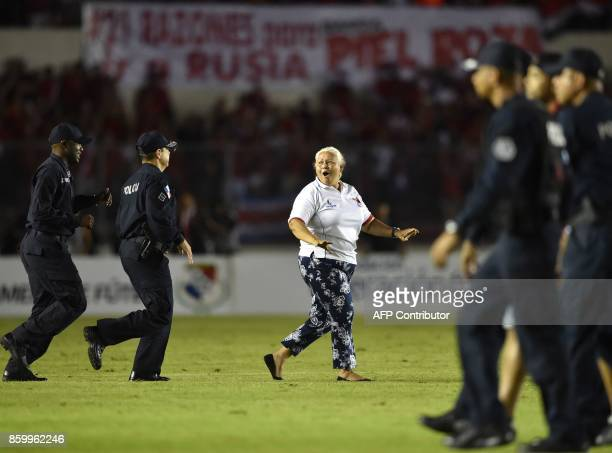 A supporter of Panama chased by police officers runs onto the field to celebrate after her team defeats Costa Rica and qualifies for the 2018 World...