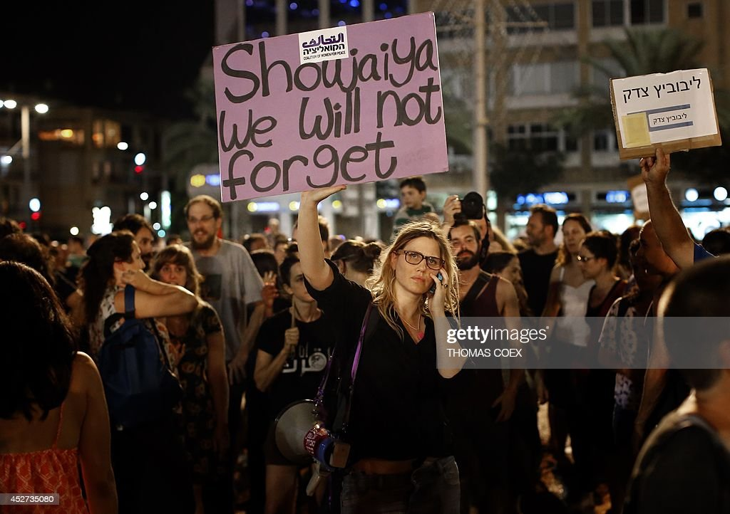 A supporter of peace raises up a placard as thousands of them gather at the Rabin Square in Tel Aviv on July 26, 2014, to ask for the end of the Israeli military offensive in the Gaza Strip. The conflict has claimed more than 1,000 Palestinian lives, most of them civilians, and has killed 40 Israeli soldiers and three civilians inside Israel.