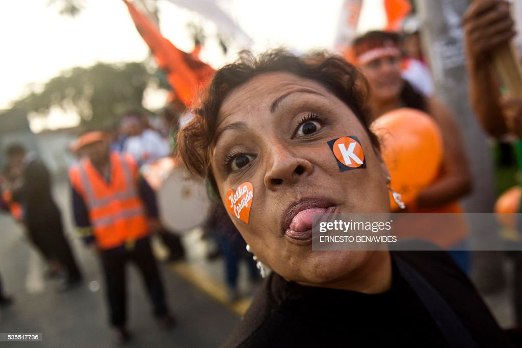 A supporter of Peruvian presidential candidate for the Fuerza Popular (Popular Strength) party Keiko Fujimori pulls her tongue before a televised debate with Pedro Pablo Kuczynski of the 'Peruanos por el Kambio' (Peruvians for change) party in Lima on May 29, 2016. Fujimori and Kuczynski will compete in Peru's June 5 runoff election. / AFP / ERNESTO