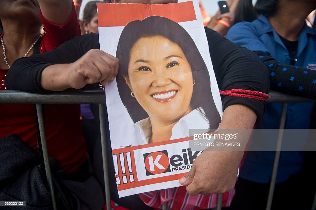 A supporter of Peruvian presidential candidate for the Fuerza Popular (Popular Force) party and daughter of imprisoned former Peruvian President (1990-2000) Alberto Fujimori, Keiko Fujimori, holds a poster of her during a campaign rally in Lima on May 31, 2016. Fujimori leads the polls for next May 5 presidential elections in Peru. / AFP / ERNESTO