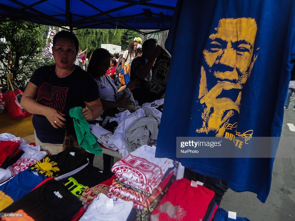 A supporter of Philippine President Rodrigo Duterte sells t-shirts bearing the president's image on Thursday, 30 June 2016, in Manila, Philippines.