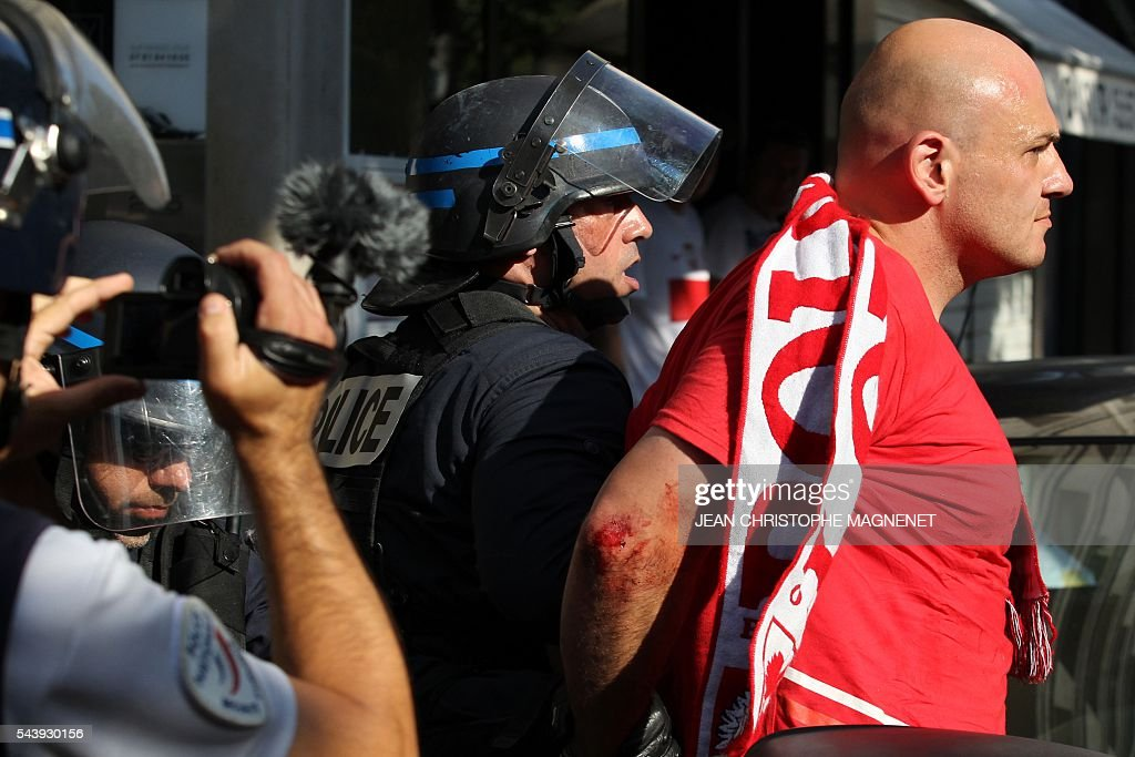 A supporter of Poland is detained by french anti riot policemen, ahead of the Euro 2016 championship match between Poland and Portugal, in Marseille, southern France, on June 30, 2016. / AFP / JEAN