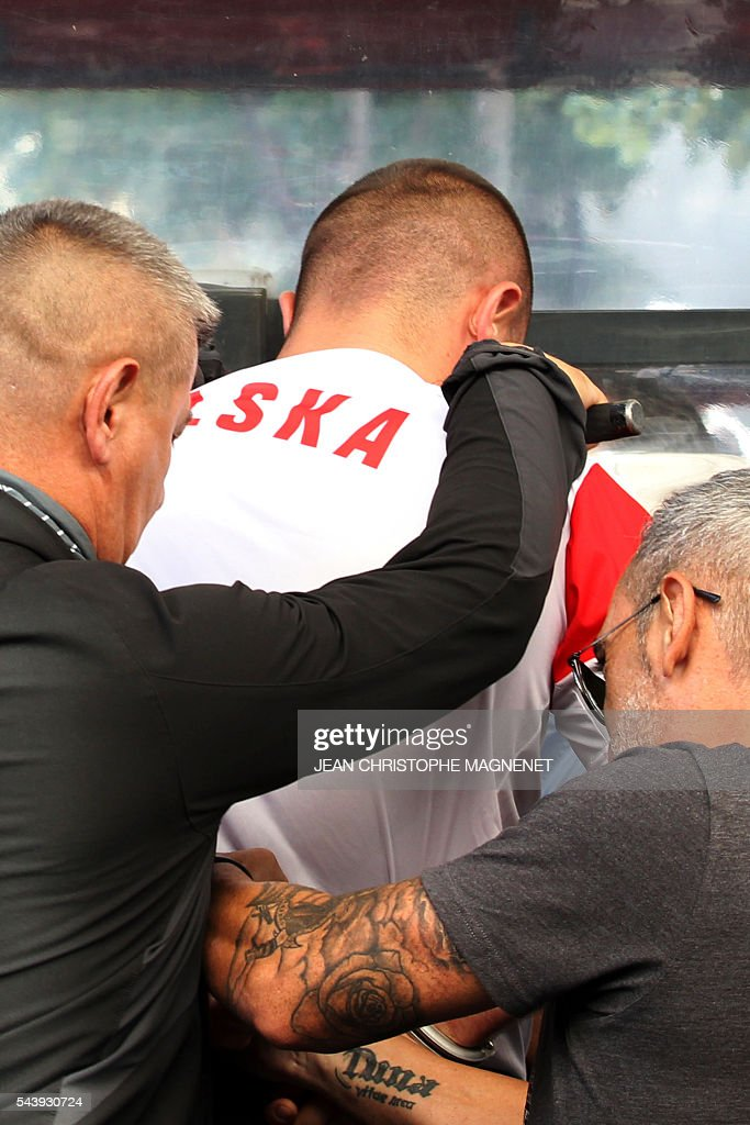 A supporter of Poland is detained by french policemen, ahead of the Euro 2016 championship match between Poland and Portugal, in Marseille, southern France, on June 30, 2016. / AFP / JEAN
