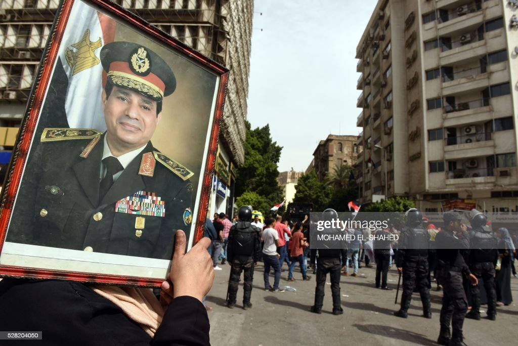 A supporter of President Abdel Fattah al-Sisi carries of portrait of him as a sign of protest against the journalists demonstrating to demand the sacking of the interior minister on May 4, 2016 outside the Journalists' Syndicate headquarters in Cairo. Egyptian police stormed the headquarters of the journalists' association in central Cairo on May 1, 2016 and arrested two journalists, Amr Badr and Mahmud el-Sakka, for incitement to protest. / AFP / MOHAMED