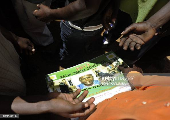 A supporter of President Barack Obama's Kenyan half brother Malik Obama distribute campaign posters on January 16 2013 at the peaceful hamlet of...