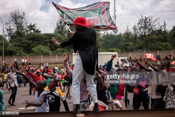 A supporter of President Uhuru Kenyatta waves Kenya's national flag as he celebrates during a demonstration on November 20 2017 in Nairobi after...
