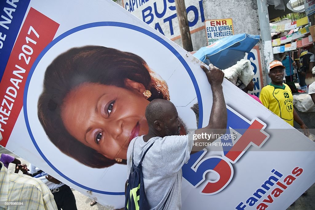 A supporter of Presidential Candidate from Lavalas Political Party Maryse Narcisse holds an electoral poster before the start of a march in support...