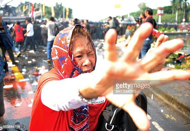 A supporter of presidential candidate Prabowo tries to make her away as police disperse a crowd with tear gas near the constitutional court in...