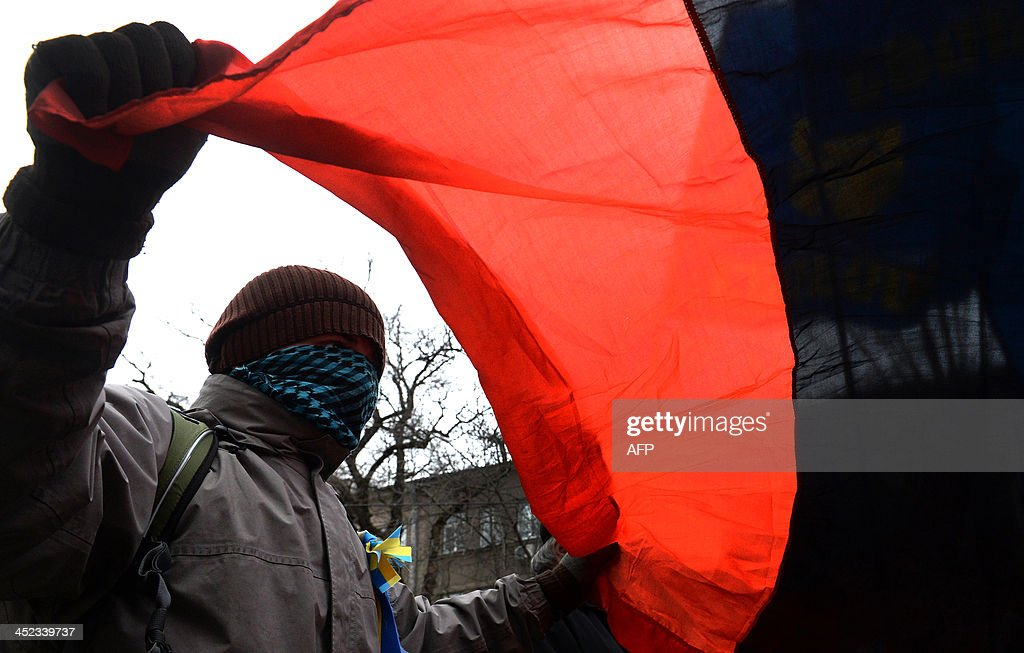A supporter of radical party Svoboda (Freedom) holds a nationalist red-black flag during a protest against political repression in front of the Ukrainian Interior Ministry headquarters in Kiev on November 28, 2013, as mass protests over a move to scrap a key pact with the EU went the day beore into a fourth day. An EU summit to cap years of effort to bring ex-Soviet states into the Western fold opens with its ambitions dented on November 28 after Ukraine, the biggest prize, balked at the last moment under Russian pressure.