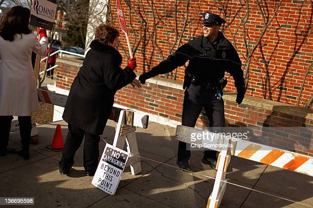 A supporter of Republican presidential candidate and former Utah Gov Jon Huntsman thanks a Manchester police officer outside the polling place at...
