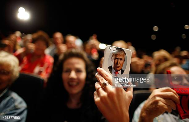 A supporter of Republican presidential candidate Donald Trump takes video on her Trumpbranded phone during a campaign rally at the Treasure Island...