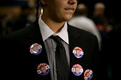 A supporter of Republican presidential candidate Donald Trump wears campaign buttons as he waits for the start of a campaign rally at the Westgate...