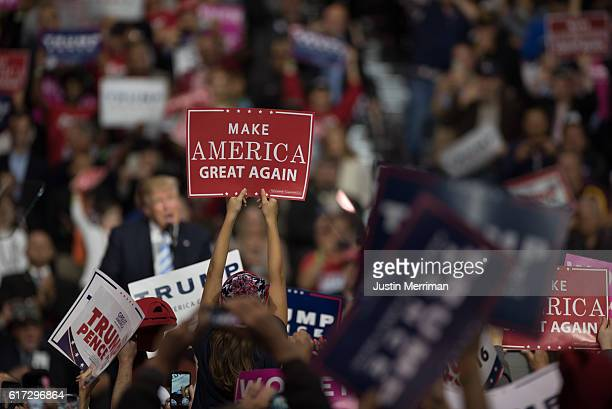 A supporter of Republican presidential nominee Donald Trump holds up a 'Make America Great Again' sign as the candidate addresses supporters during a...