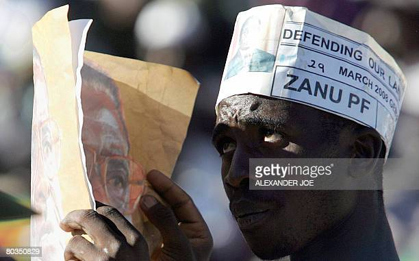 A supporter of Robert Mugabe leader of Zimbabwe's ruling National Africa Union Patriotic Front peers at him over a poster as Mugabe addresses a rally...
