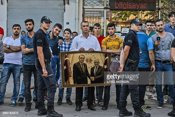 TOPSHOT A supporter of ruling Justice and Development Party holds a carpet poster of Turkish President and Prime Minister during a rally on September...