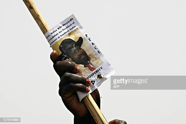 A supporter of Salva Kiir the President of Southern Sudan and Vicepresident of Sudan holds high a pamphlet with Kiir's image during a political rally...