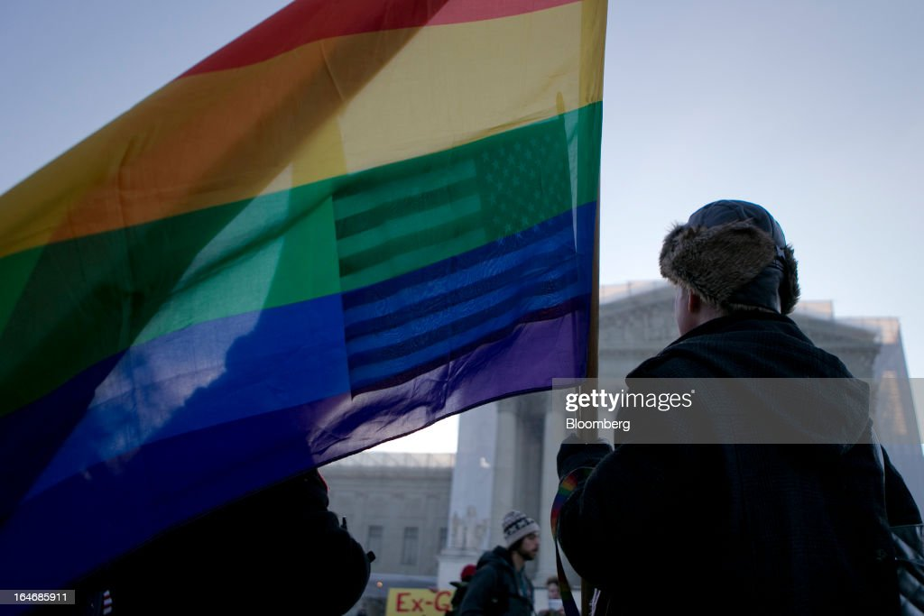 A supporter of same-sex marriage holds a rainbow flag while demonstrating outside the U.S. Supreme Court in Washington, D.C., U.S., on Tuesday, March 26, 2013. The Supreme Court takes up what is probably its biggest civil-rights dispute in decades this week when it hears arguments that could lead to the legalization of same-sex marriage nationwide. Photographer: Andrew Harrer/Bloomberg via Getty Images