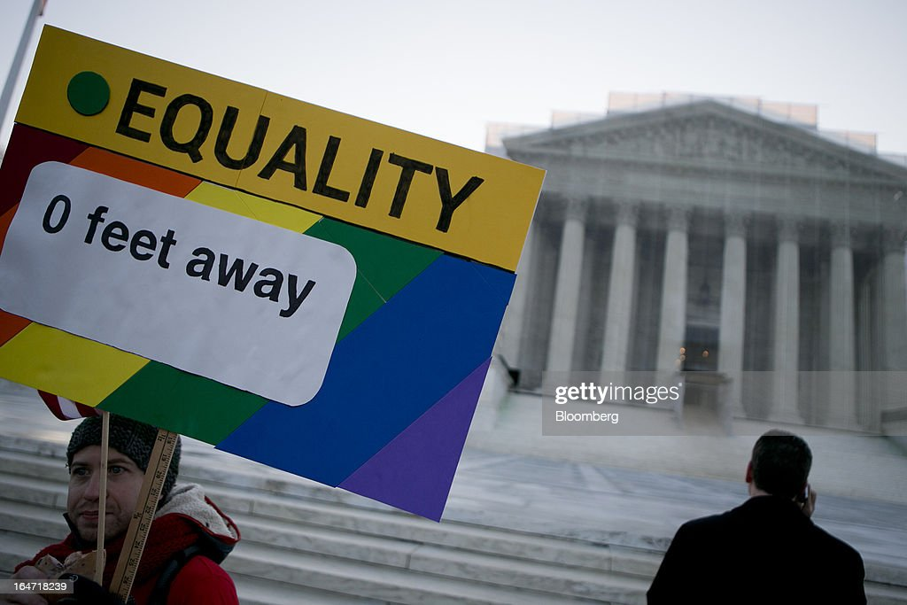 A supporter of same-sex marriage holds a sign in front of the U.S. Supreme Court in Washington, D.C., U.S., on Tuesday, March 26, 2013. The Supreme Court takes up what is probably its biggest civil-rights dispute in decades this week when it hears arguments that could lead to the legalization of same-sex marriage nationwide. Photographer: Andrew Harrer/Bloomberg via Getty Images