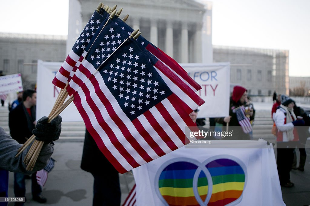 A supporter of same-sex marriage holds U.S. flags in front of the U.S. Supreme Court in Washington, D.C., U.S., on Tuesday, March 26, 2013. The Supreme Court takes up what is probably its biggest civil-rights dispute in decades this week when it hears arguments that could lead to the legalization of same-sex marriage nationwide. Photographer: Andrew Harrer/Bloomberg via Getty Images