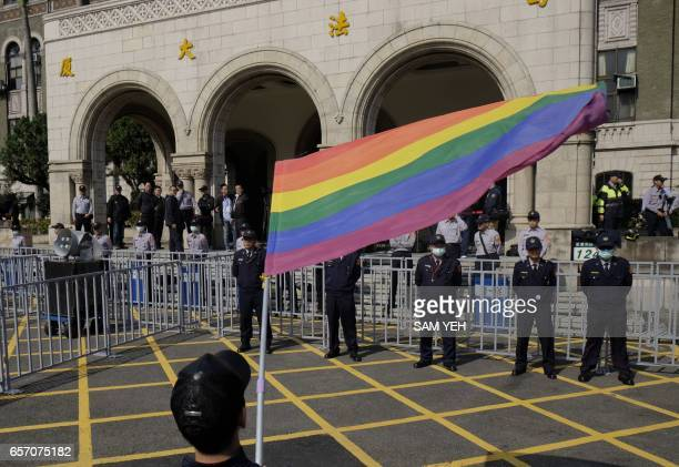 A supporter of samesex marriage waves a flag outside the Judicial Yuan in Taipei on March 24 2017 Taiwan's constitutional court began hearing a...