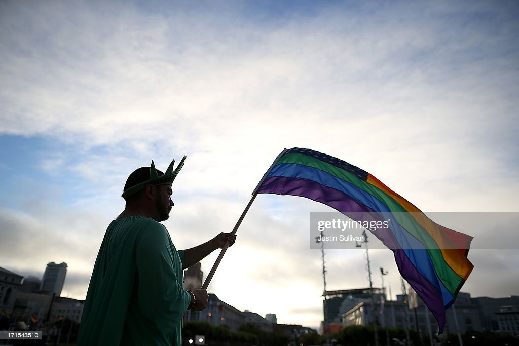 A supporter of same-sex marriage waves a pride flag in front of San Francisco City Hall before the announcement of the results of the U.S. Supreme Court's rulings on gay marriage in City Hall June 26, 2013 in San Francisco, California. The high court struck down the Defense of Marriage Act (DOMA) and ruled that supporters of California's ban on gay marriage, Proposition 8, could not defend it before the Supreme Court.