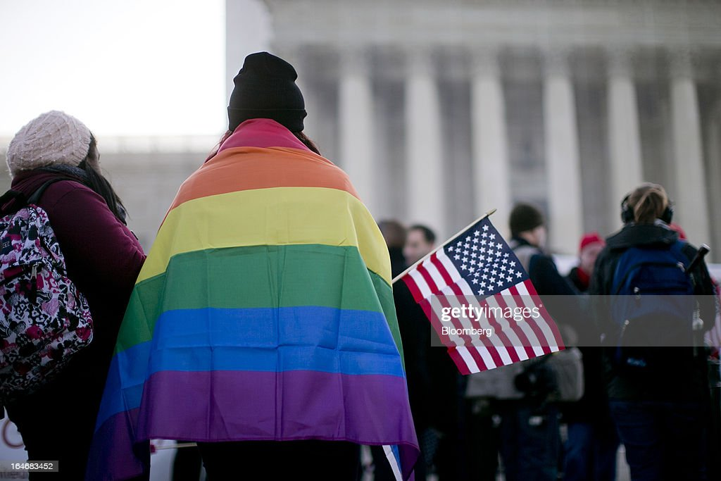 A supporter of same-sex marriage wears a rainbow flag in front of the U.S. Supreme Court in Washington, D.C., U.S., on Tuesday, March 26, 2013. The Supreme Court takes up what is probably its biggest civil-rights dispute in decades this week when it hears arguments that could lead to the legalization of same-sex marriage nationwide. Photographer: Andrew Harrer/Bloomberg via Getty Images
