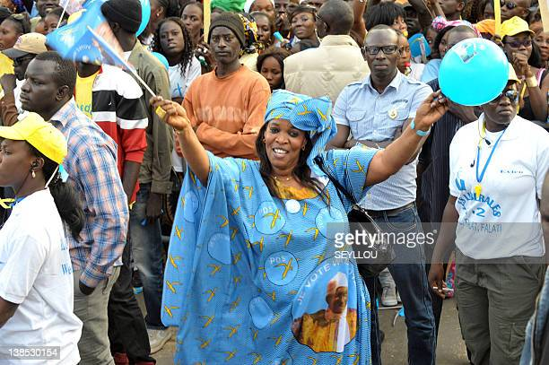 A supporter of Senegal's leader Abdoulaye Wade wearing a blue and gold flowing boubou reflecting party colours dances during a rally in Thies on...