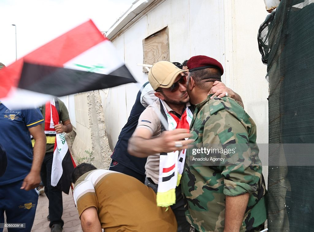 Supporter of Shia cleric Muqtada al-Sadr kisses a guard at check point after entering into highly-fortified Green Zone in Baghdad, Iraq on April 30, 2016.