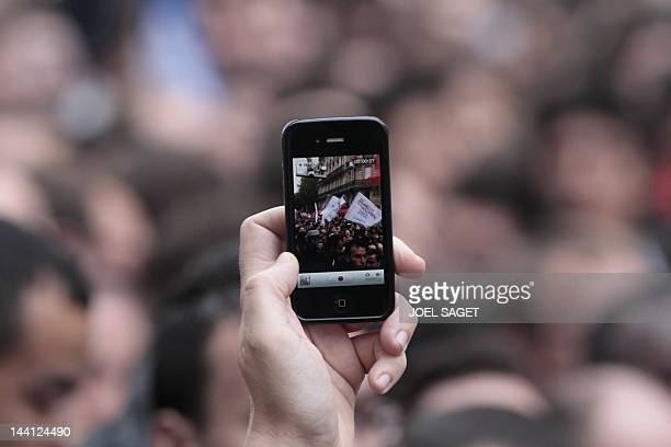 A supporter of Socialist Party candidate for the 2012 French presidential election Francois Hollande films with a mobile phone people gathered on May...