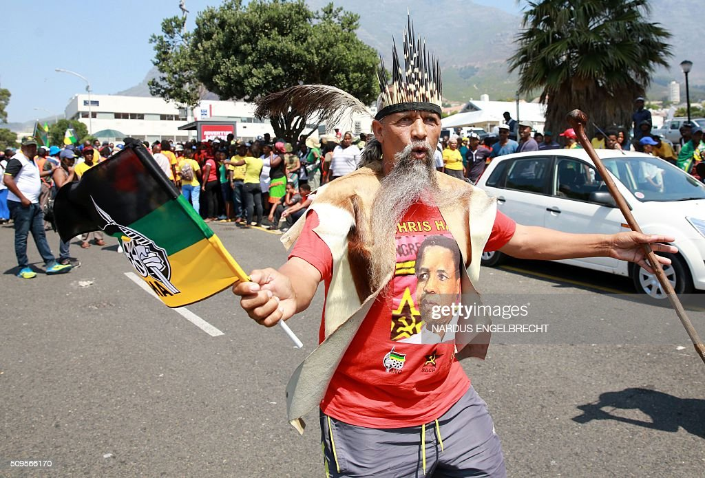 A supporter of South Africa's African National Congress ruling party and President Jacob Zuma shows his support for the president on February 11, 2016, in Cape Town, South Africa few hours ahead of his State of the Nation address. Police manned razor wire barricades outside the South African parliament on February 11 ahead of President Jacob Zuma's address to the nation against a background of concerted efforts to oust him from office. The embattled president faces moves in court, in parliament and on the streets to have him impeached or dumped by the ruling African National Congress (ANC). ENGELBRECHT