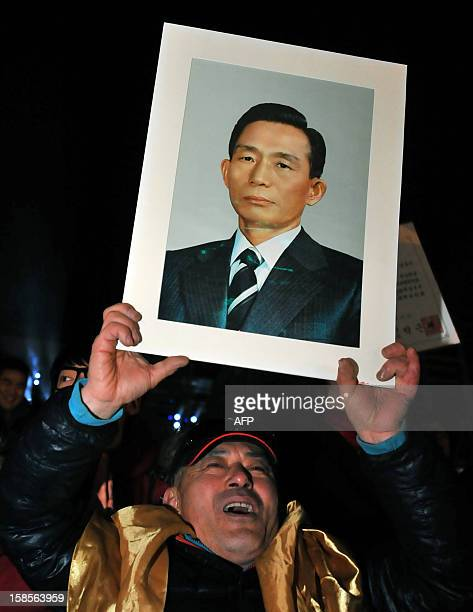 A supporter of South Korea's presidentelect Park GeunHye of the ruling New Frontier Party holds up a portrait of Park's father Park ChungHee the...