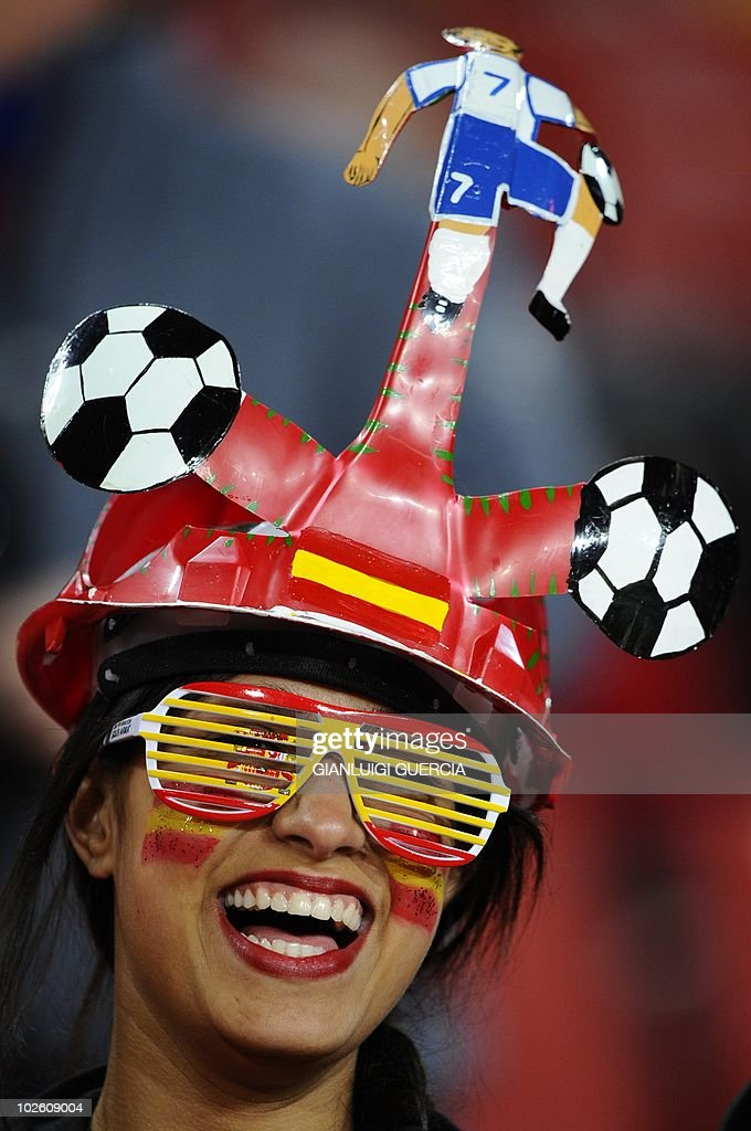 A supporter of Spain with glasses designed with the country's colours and wearing a makarapa hat smiles before the start of the 2010 World Cup...
