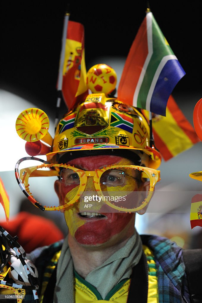 A supporter of Spain with the national colours on his face and wearing a makarapa flying a Spanish and a South African flag stands outside Ellis Park...