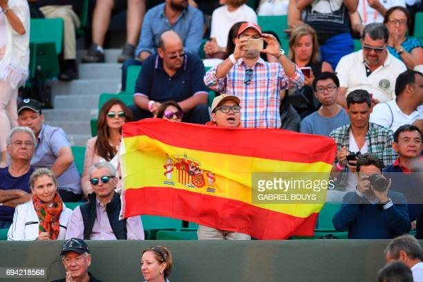 A supporter of Spain's Rafael Nadal waves a national flag as he plays against Austria's Dominic Thiem during their semifinal tennis match at the...