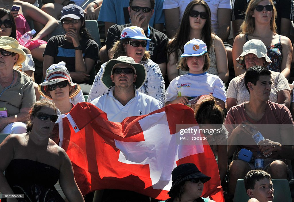A supporter of Stanislas Wawrinka of Switzerland holds up the Swiss flag during his men's singles first round match against Benoit Paire of France on day one of the 2012 Australian Open tennis tournament in Melbourne on January 16, 2012. IMAGE
