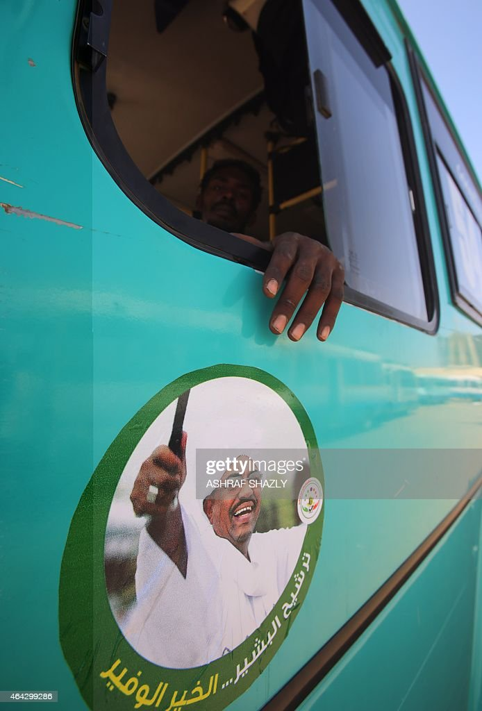 A supporter of Sudanese President Omar al-Bashir (portrait) sits in a bus bearing an image of the incumbent president during an electoral campaign rally in Khartoum on February 24, 2015, ahead of the April 13 parliamentary and presidential elections. Campaigning for Sudan's elections started in February 22 with Omar al-Bashir facing little competition for the presidency, a multi-party boycott and the opposition and press facing mounting repression.