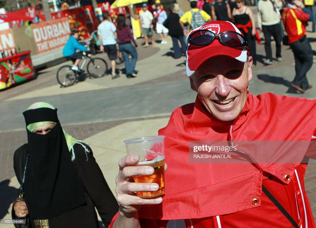 A supporter of Switzerland, standing near a veiled resident, holds a glass of beer while hundreds of colourful Swiss fans from all over the world descend on the Fanfest at the New North Beach in Durban, on 16 June, 2010 to watch the 2010 Football World Cup match between Switzerland and Spain.