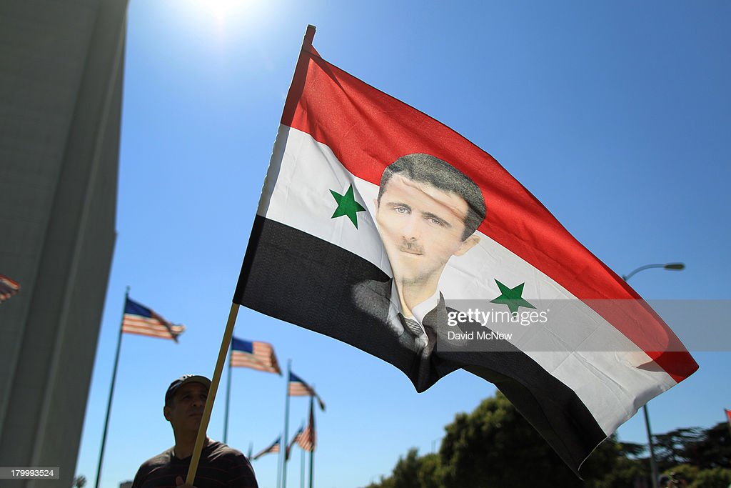 A supporter of Syrian president Bashar Hafez al-Assad waves a flag bearing a picture of the president at a rally to urge Congress to vote against a limited military strike against the Syrian military in response to allegations that Assad has used sarin gas to kill civilians on September 7, 2013 in Los Angeles, California. The Obama administration claims to have clear evidence that the Syrian military broke international law by killing nearly 1,500 Syrian civilians, including at least 426 children, in a chemical weapons attack on August 21, and is seeking the support of Congress for a missile strikes to prevent future chemical weapons attacks by the regime and other nations.