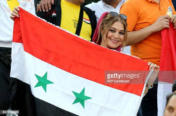 A supporter of Syria's national team attends the FIFA World Cup 2018 qualification football match between Syria and Iran at the Azadi Stadium in...