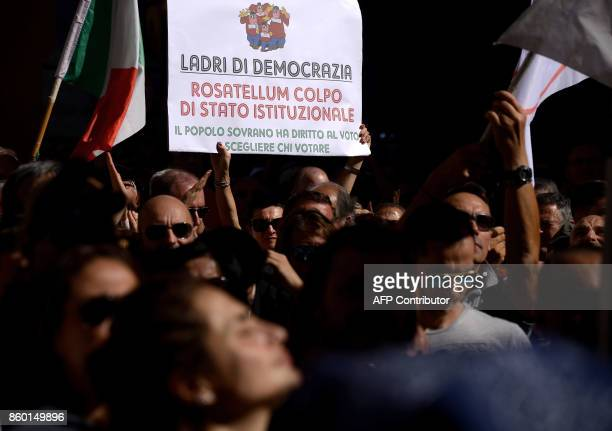 A supporter of the antiestablishment 5Star Movement holds a sign reading 'Thieves of democracy Rosatellum Institutional coup the sovereign people...