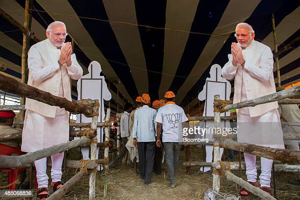 Supporter of the Bharatiya Janata Party walk past paper cut outs of Indian Prime Minister Narendra Modi during a rally in Muzaffarpur Bihar India on...